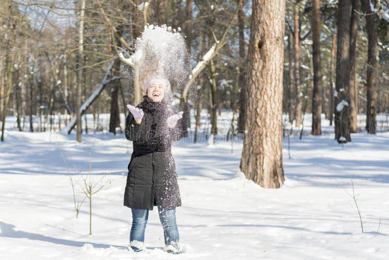 Lycklig flicka för vintersnökamp som kastar snö som utanför spelar Glad ung kvinna som har gyckel i naturen Forest Park på snöig  arkivbild