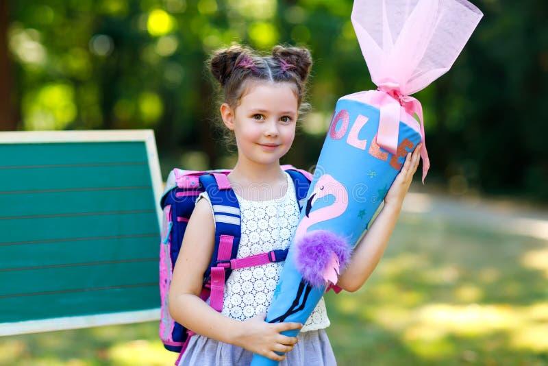 Lycklig flicka f?r liten unge vid skrivbordet med ryggs?cken eller axelv?ska och stor skolap?se eller kotte som ?r traditionell i arkivfoto