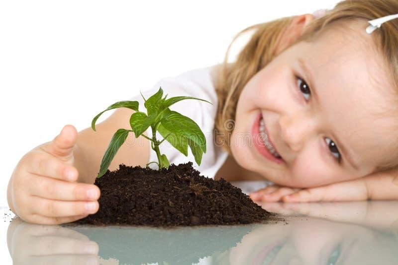 lycklig flicka henne little växt royaltyfri bild