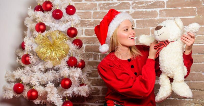 Lycklig flicka i den Santa Claus hatten Parti för nytt år Leveransjulgåvor Le kvinnan som firar jul glatt arkivfoton