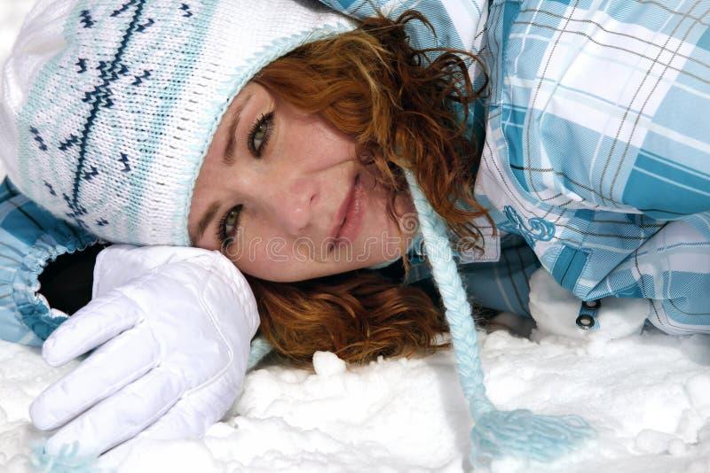 Lycklig flicka i ett mörkt - blått skidar dräkten lägger i snö fotografering för bildbyråer