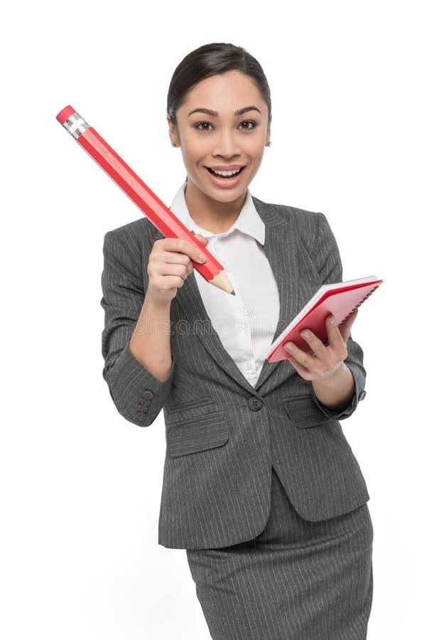 Lycklig flicka i Grey Suit med den jätte- blyertspennan och blocket av papper royaltyfria bilder