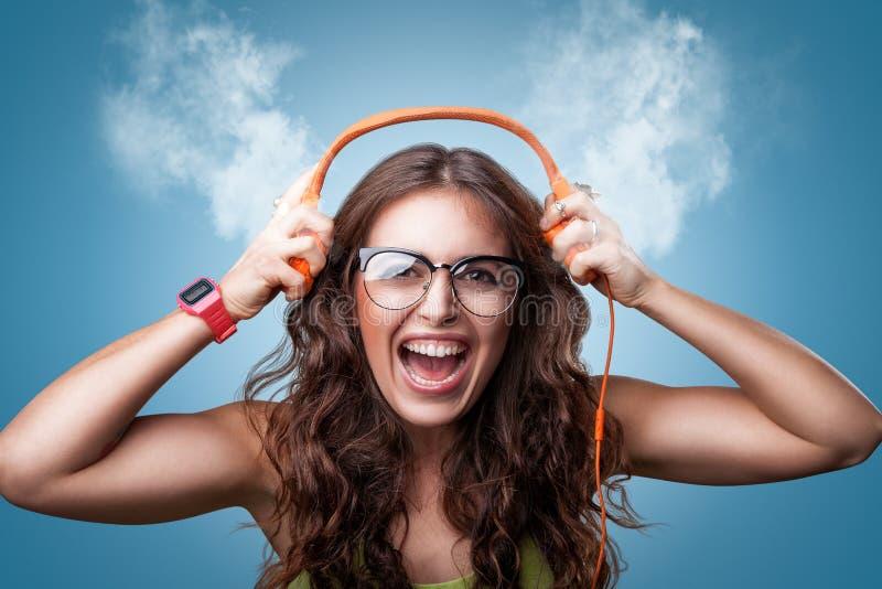 Lycklig flicka i hörlurar som lyssnar till musik royaltyfria bilder