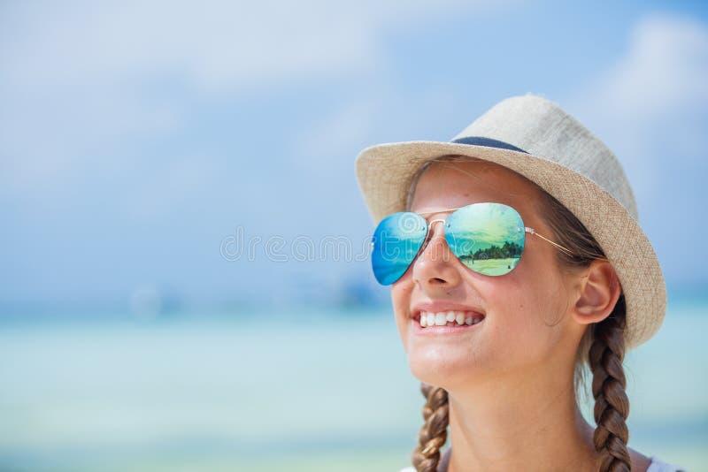 Lycklig flicka i hatt och solglasögon på stranden Resa resväskan med seascapeinsida royaltyfri foto