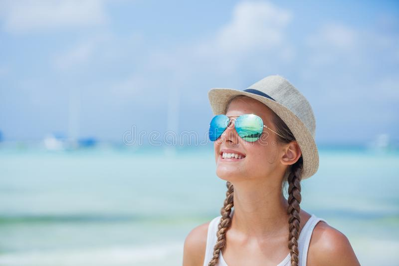 Lycklig flicka i hatt och solglasögon på stranden Resa resväskan med seascapeinsida royaltyfria bilder