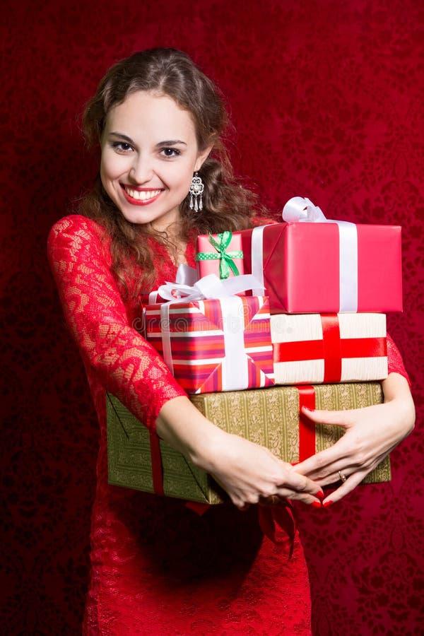Lycklig flicka i röd klänning med gåvaasken arkivbild