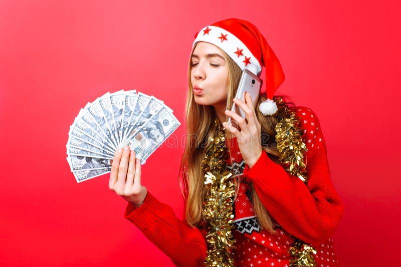 Lycklig flicka i röd tröja och jultomtenhatt som talar på telefon- och innehavpengar i handen som försöker att kyssa dem, på röd  royaltyfri fotografi