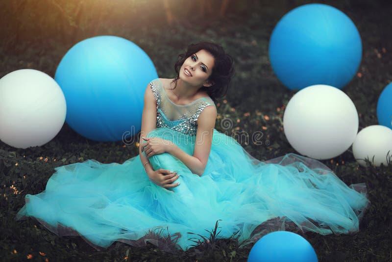 Lycklig flicka i studentbal med heliumluftballonger Den härliga flickakandidaten i en blå klänning sitter på gräset nära a royaltyfria bilder