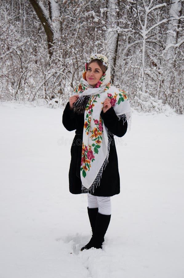 Lycklig flicka i vintern i parkera Ukrainsk kvinna i traditionell halsduk- och blommakrans royaltyfri fotografi
