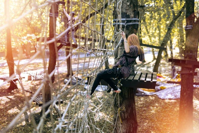 Lycklig flicka, kvinna som klättrar kugghjulet i ett affärsföretag, repväg, försäkring, dragning, nöjesfält, aktiv rekreation, hö arkivbild