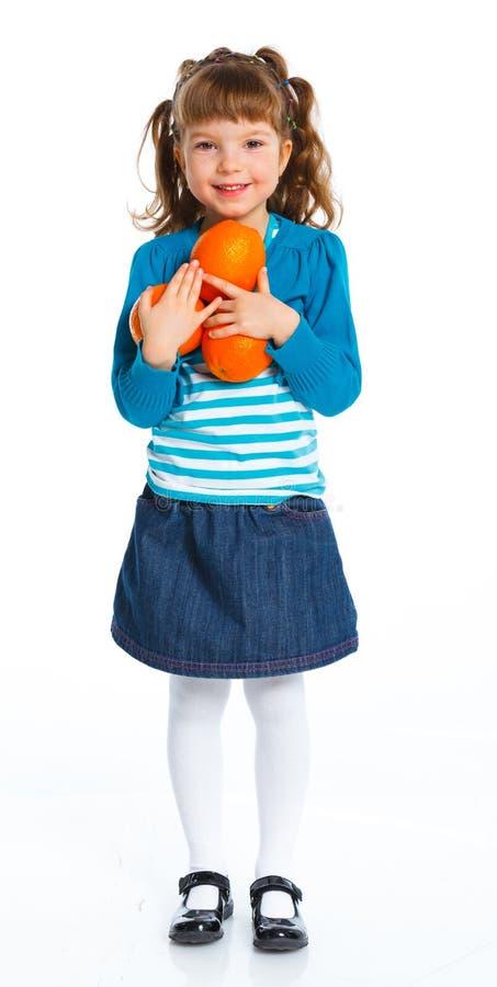 Lycklig flicka med apelsiner fotografering för bildbyråer