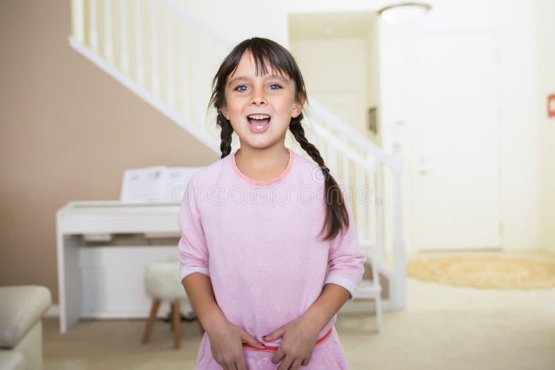 Lycklig flicka med blåa ögon och flätat hår arkivfoto