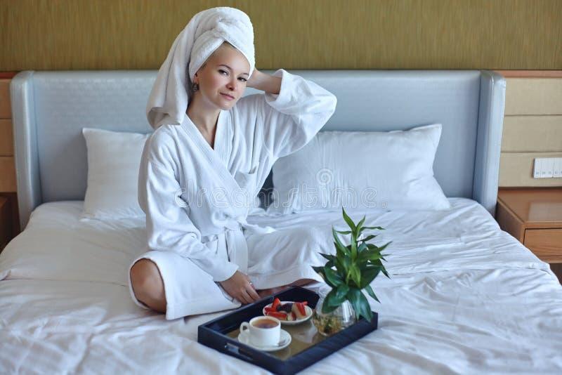 Lycklig flicka med en kopp kaffe Badrock och handduk f?r hem- stilavkopplingkvinna b?rande efter dusch Spa bra morgon royaltyfri foto