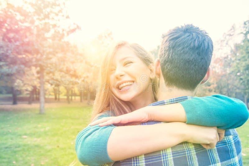 Lycklig flicka med ett förälskat leende krama hennes pojkvän royaltyfri fotografi