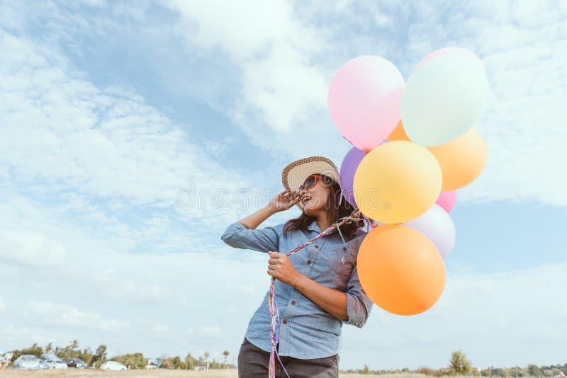 Lycklig flicka med färgrika ballonger, i ängarna arkivfoto