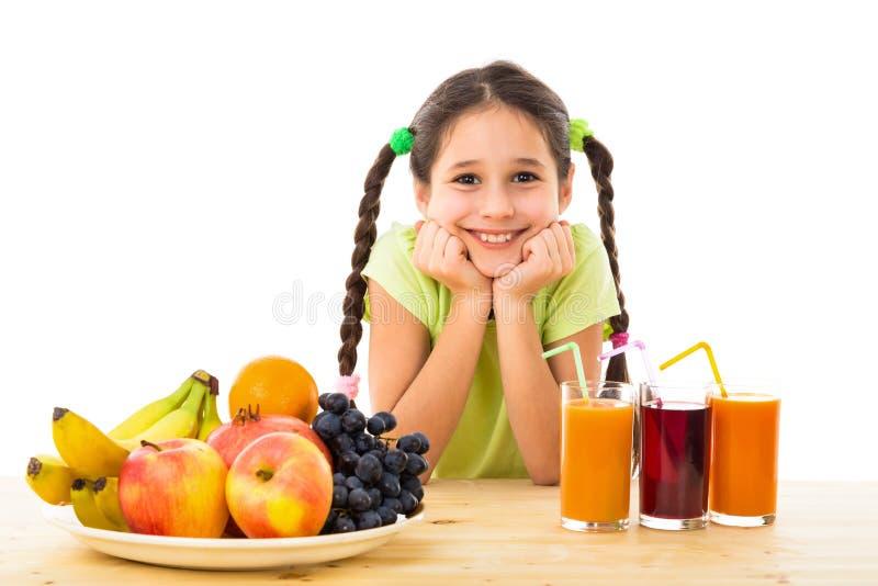 Lycklig flicka med frukter och fruktsaft royaltyfria bilder