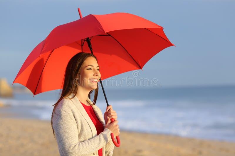 Lycklig flicka med hållande ögonen på solnedgång för rött paraply på stranden royaltyfri foto