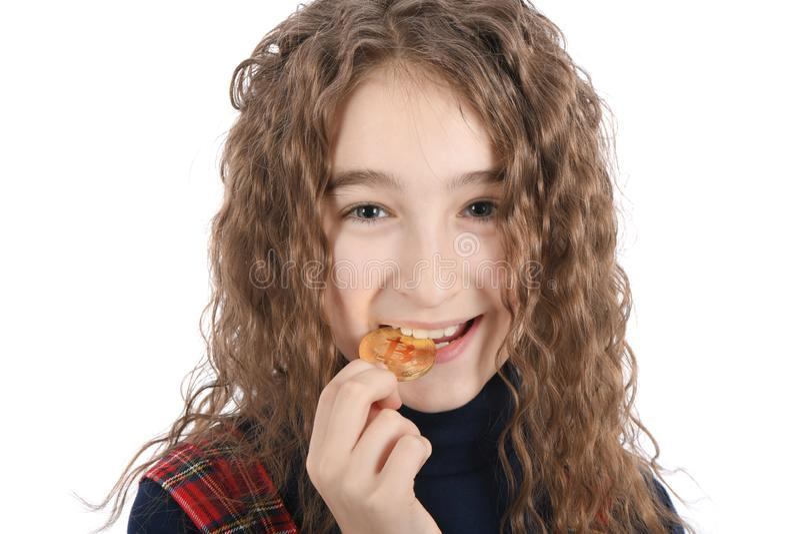 Lycklig flicka med långa uppehällen för lockigt hår och försöka att smaka guld- cryptocurrencybitcoin på vit royaltyfria bilder