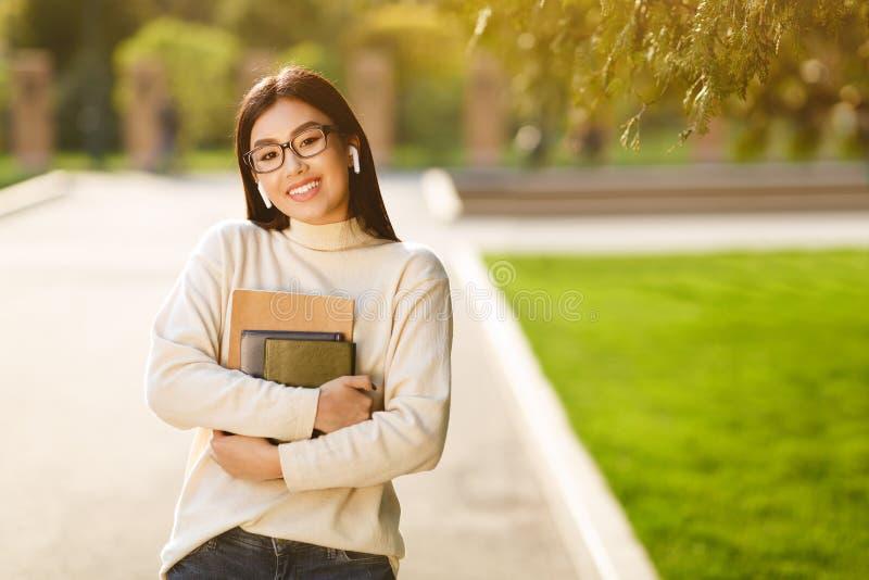 Lycklig flicka med lyssnande musik för böcker i universitetsområde royaltyfri bild