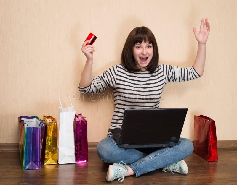 Lycklig flicka med shoppingpåsar som sitter på golvet med bärbar dator a arkivbild