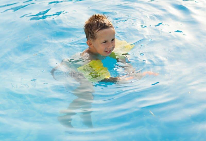 Lycklig flicka med skyddsglasögon i simbassäng arkivfoto
