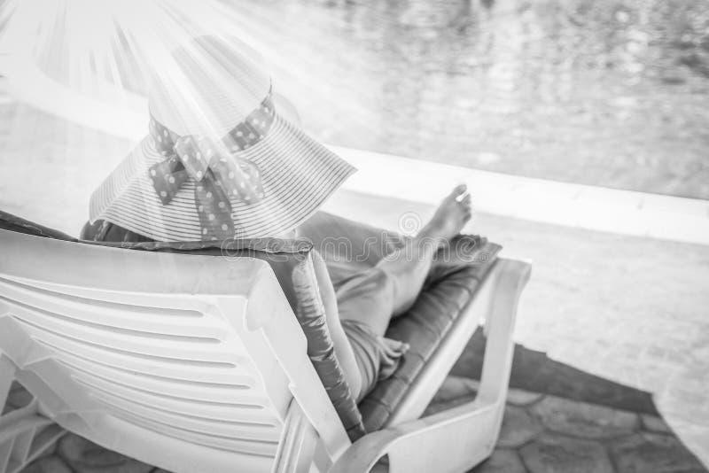 Lycklig flicka på en deckchair vid pölen vid havet royaltyfria bilder