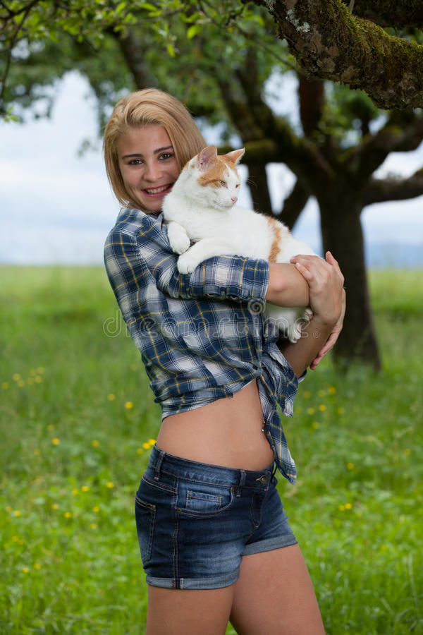 Lycklig flicka på en sommarblommaäng som rymmer en katt arkivbilder