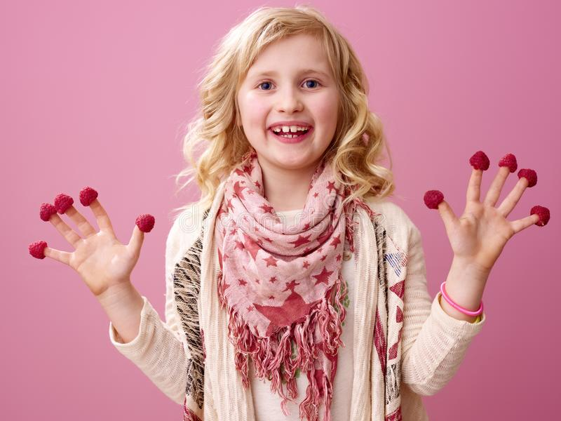 Lycklig flicka på rosa bakgrundsvisninghallon på fingrar arkivbilder