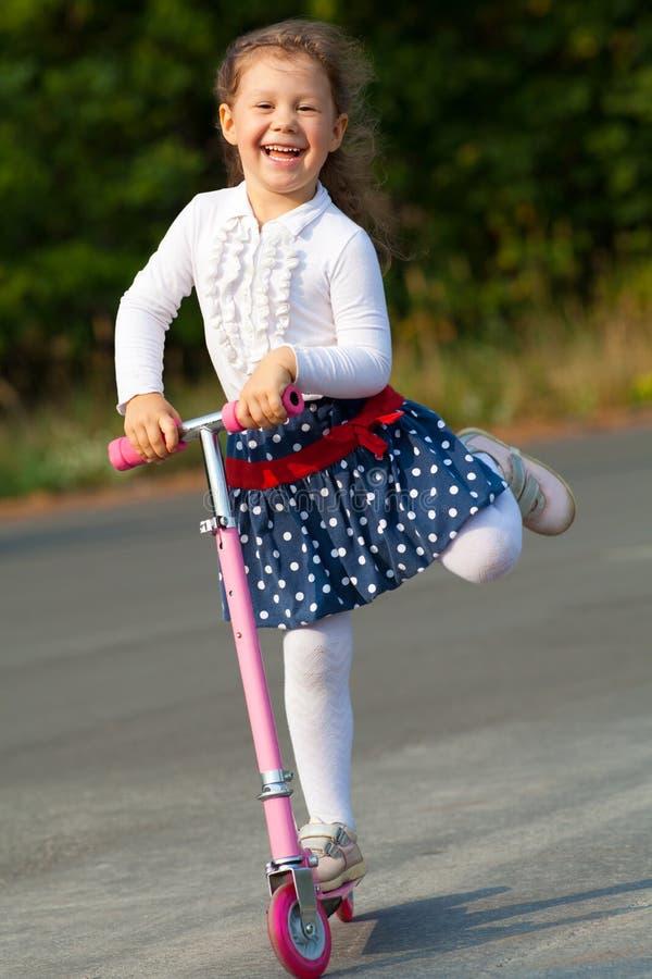 Lycklig flicka på sparkcykeln arkivfoto
