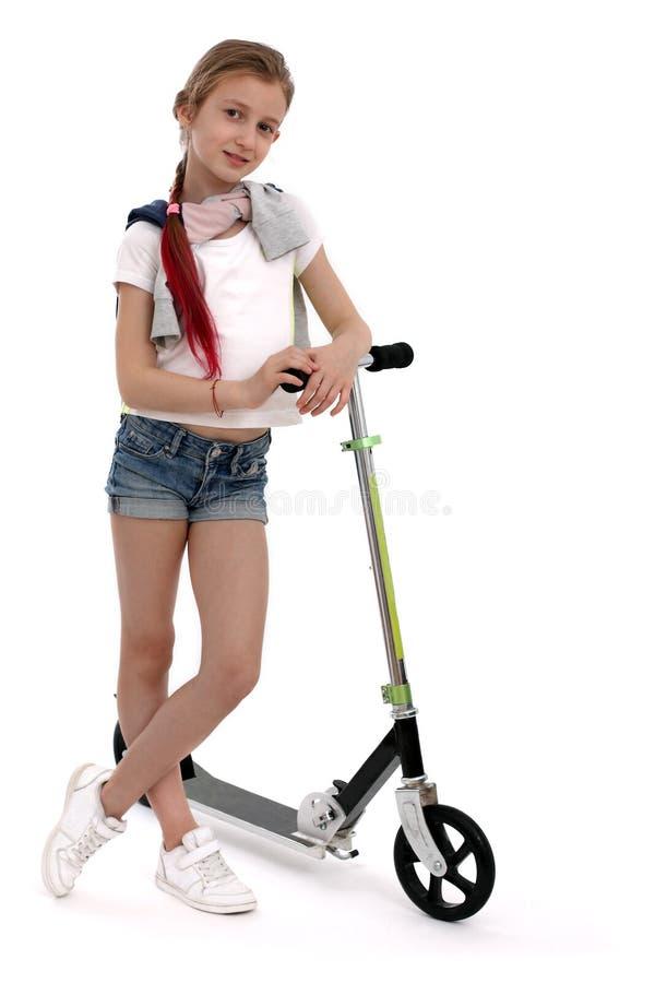 Lycklig flicka på sparkcykeln som isoleras på vit arkivfoton