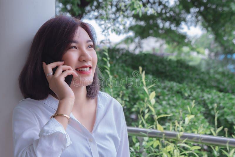 Lycklig flicka` s som ler och använder telefonmobilen, talande smart telefon på den trevliga dagen royaltyfria foton