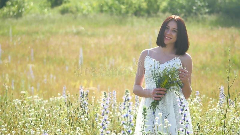 Lycklig flicka som är utomhus- i ett fält med blommor i natur flicka i ett fält som ler kvinnan som rymmer en bukett av blommor royaltyfri foto