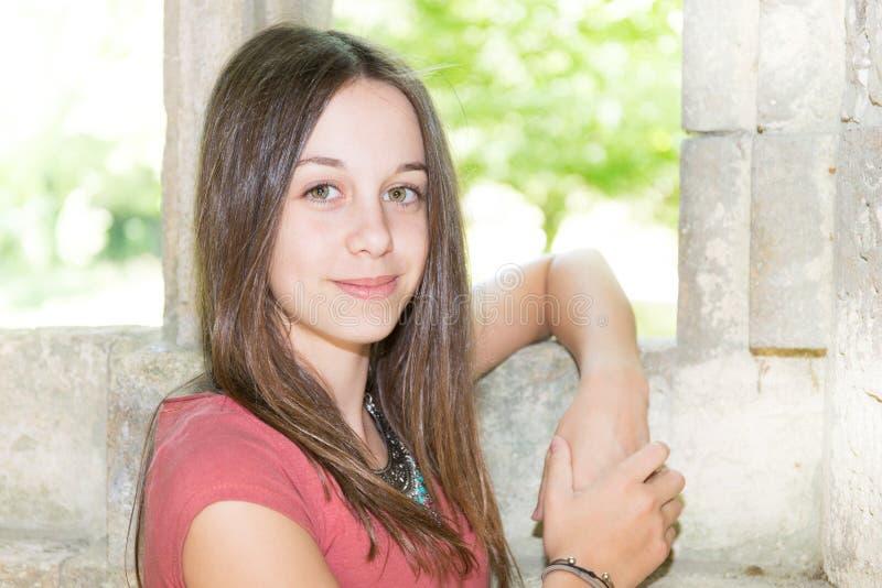 Lycklig flicka som är utomhus- med den forntida väggen i sommar royaltyfri foto