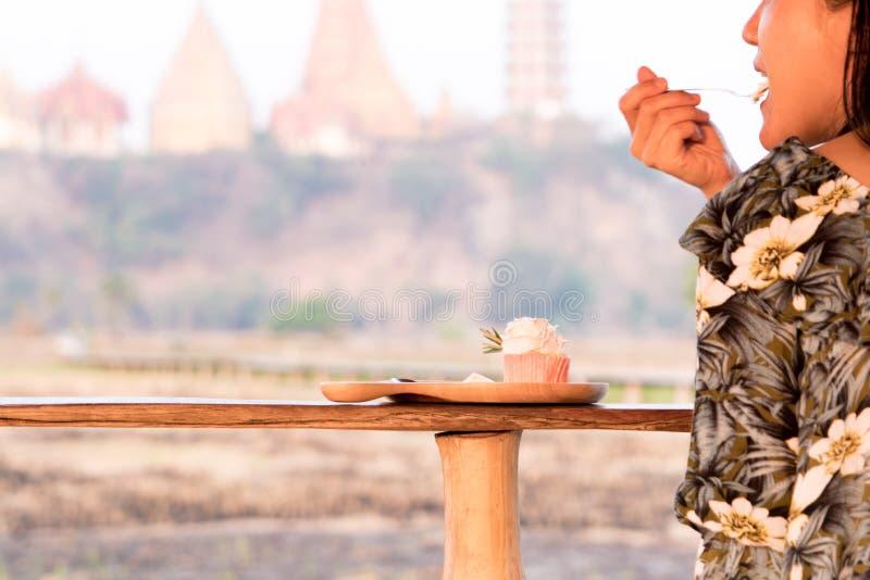 Lycklig flicka som äter den smakliga gulliga muffin på trätabellen royaltyfri foto