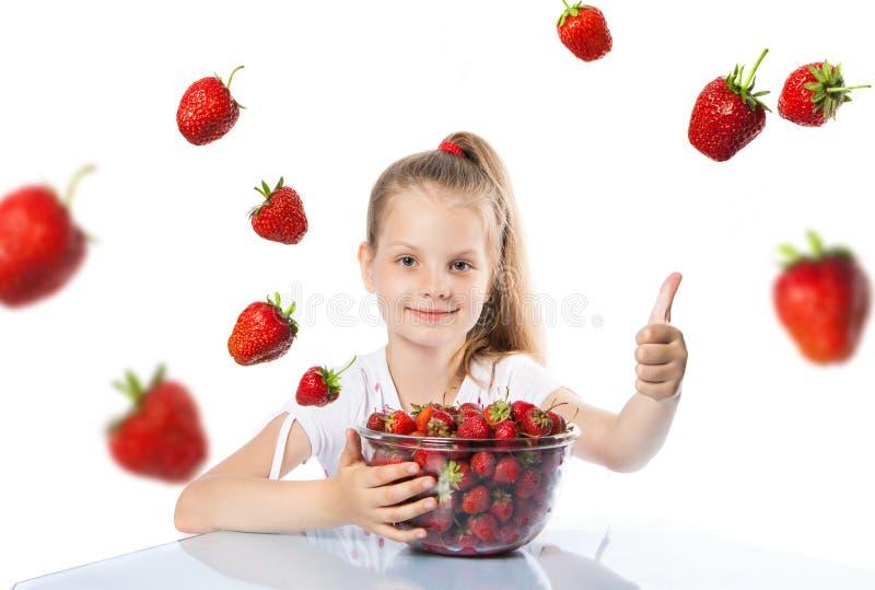 Lycklig flicka som äter jordgubbar royaltyfria bilder