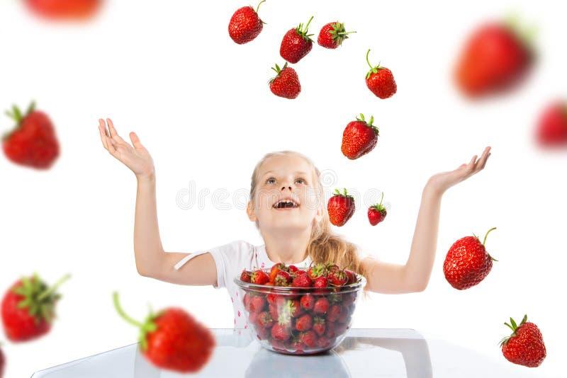 Lycklig flicka som äter jordgubbar arkivbilder