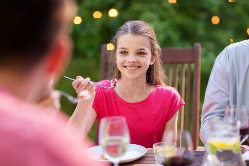 Lycklig flicka som äter med familjen på sommarträdgården arkivbild