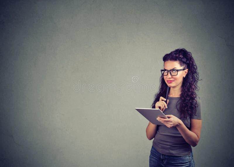 Lycklig flicka som använder blocket och att drömma royaltyfri bild