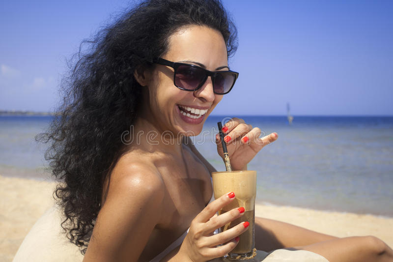 Lycklig flicka som dricker med is kaffe på stranden fotografering för bildbyråer