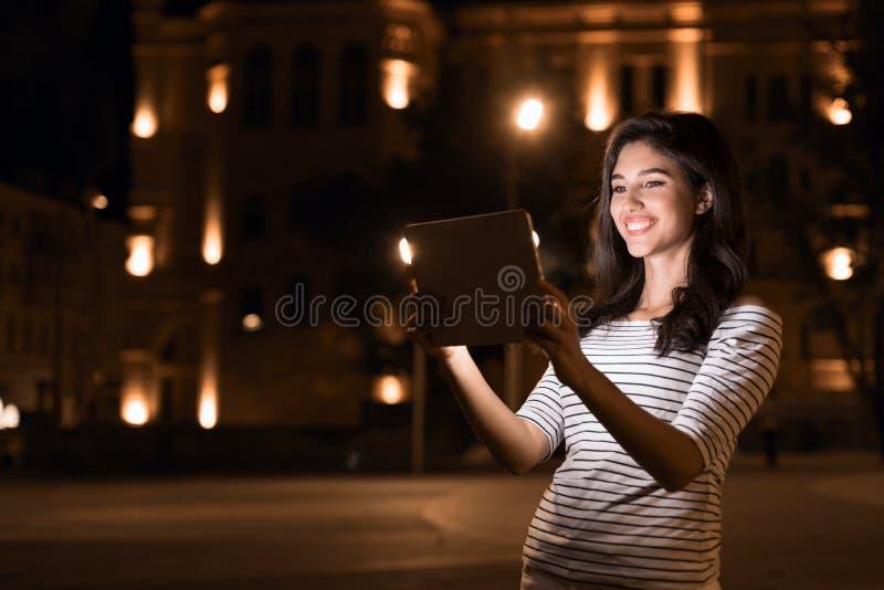 Lycklig flicka som gör video-appell på minnestavlan i nattstad arkivbild