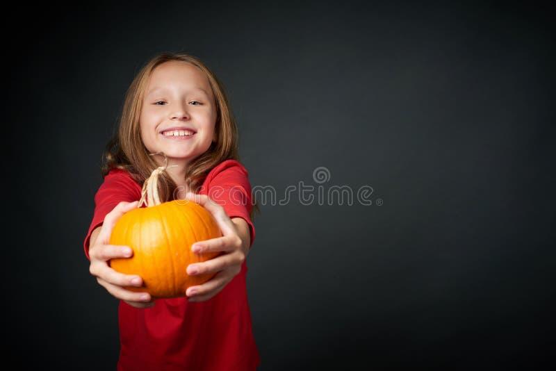 Lycklig flicka som ger dig en mogen pumpa royaltyfri foto