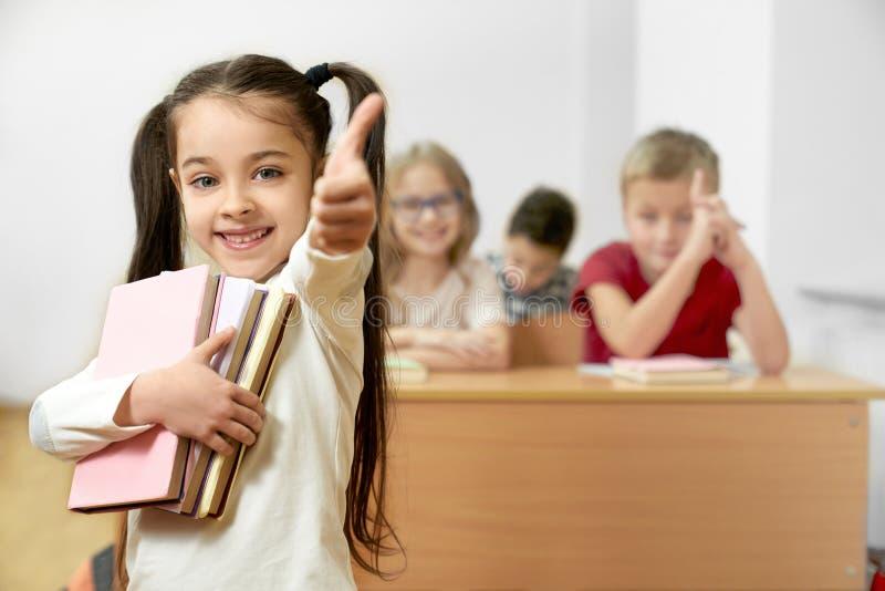 Lycklig flicka som håller böcker och visar det ok tecknet, medan stå arkivfoton