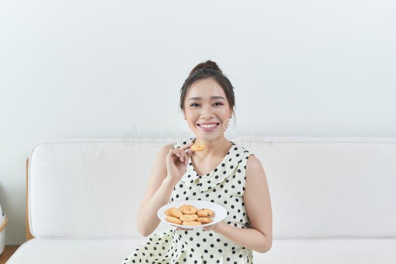 Lycklig flicka som hemma ?ter ett dietiskt kakasammantr?de p? en soffa arkivfoto