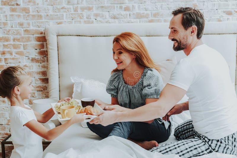 Lycklig flicka som kommer med frukosten till föräldrar i säng arkivbilder
