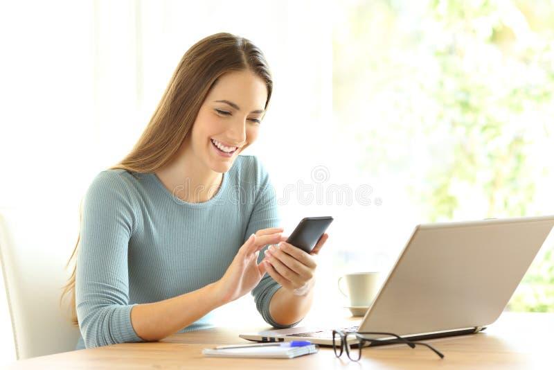 Lycklig flicka som kontrollerar på linjen innehåll på en smart telefon arkivfoto