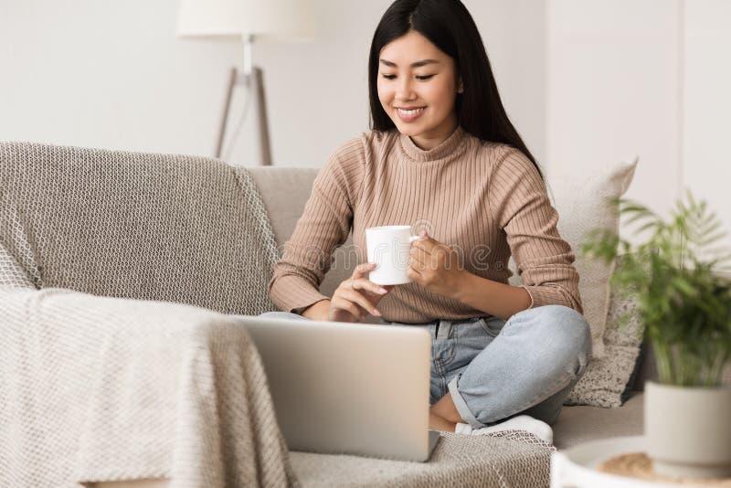 Lycklig flicka som kopplar av på den bekväma soffan och använder bärbara datorn arkivfoton