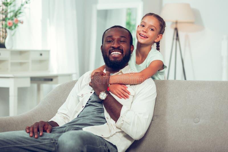 Lycklig flicka som kramar den stiliga skratta Afro--amerikan farsan på soffan royaltyfri foto