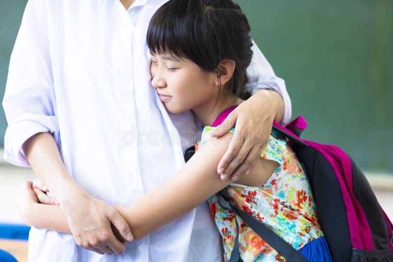 Lycklig flicka som kramar hennes moder i klassrum royaltyfri fotografi