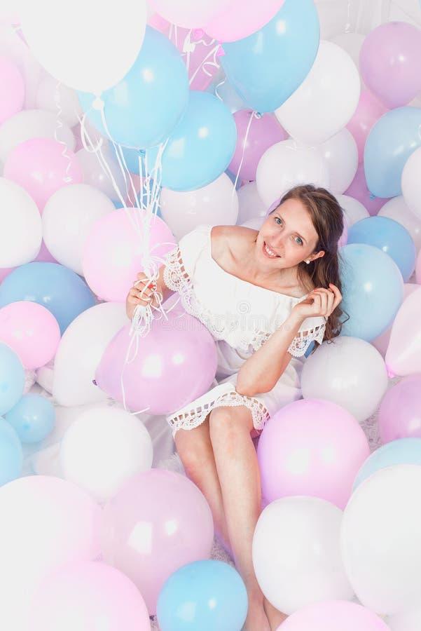 Lycklig flicka som ler, massor av bollar, studio arkivbild