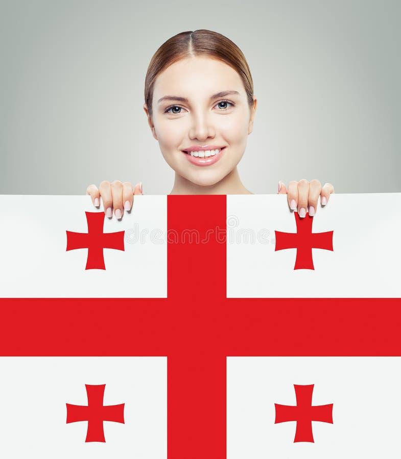 Lycklig flicka som ler studenten med Georgia flaggabakgrund royaltyfri fotografi